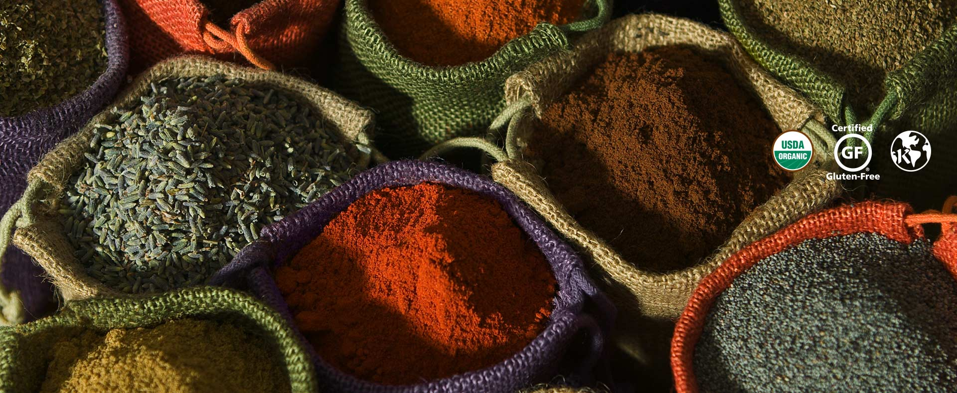 Fresh organic spices in colorful burlap bags